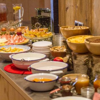 Reichhaltiges Frühstück mit Speck, Wurst, Müsli selbstgemachten Marmeladen